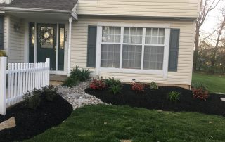 fresh mulch in front of tan house