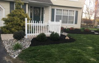 landscaping in front of tan house