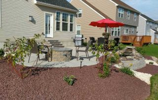 landscaped backyard wtih red umbrella