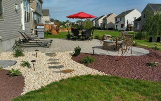 landscaped backyard with red umbrella